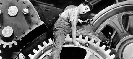 Locandina: Charlie Chaplin con maglietta con logo CNIPA mentre aggiusta degli ingranaggi